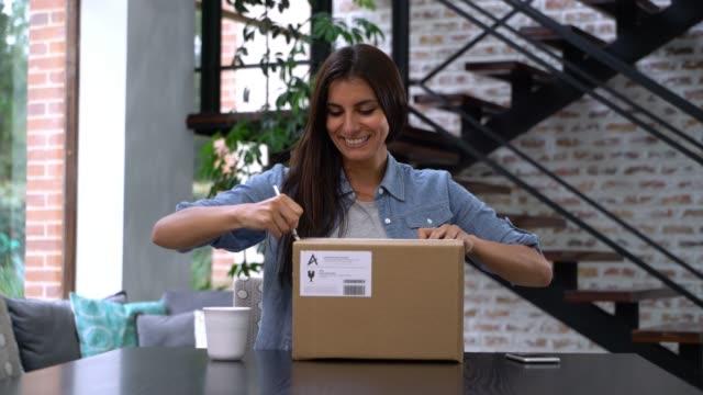 自宅で美しい女性が小包を受け取り、オープンボックスは非常に幸せ - オンラインショッピング点の映像素材/bロール