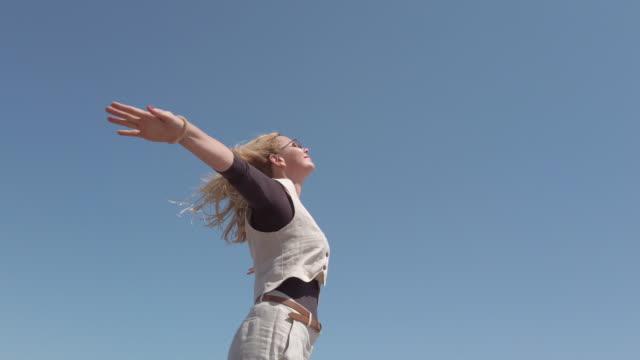 stockvideo's en b-roll-footage met mooie vrouw op het strand in een winderige dag - mid volwassen vrouw