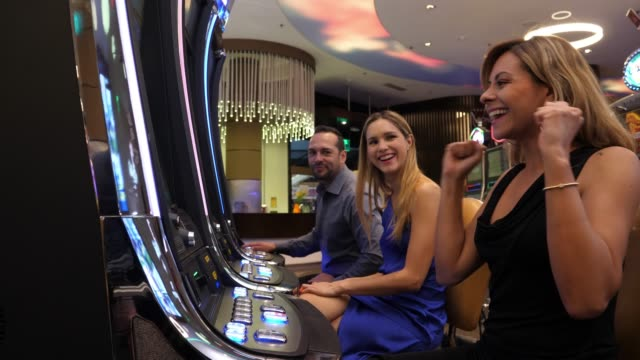 beautiful woman at the casino celebrating a win on slot machines applauding and smiling - gioco d'azzardo video stock e b–roll