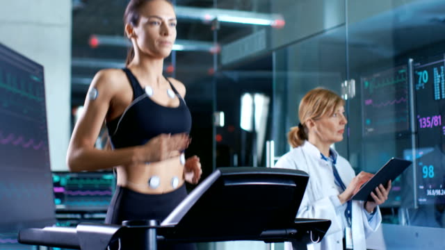 beautiful woman athlete runs on a treadmill with electrodes attached to her body, female physician uses tablet computer and controls ekg data showing on laboratory monitors. - sports medicine stock videos and b-roll footage