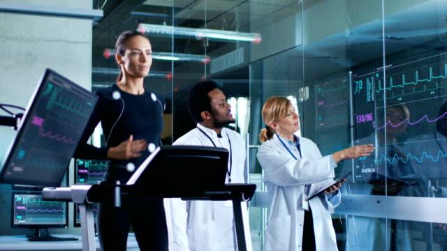 vídeos de stock, filmes e b-roll de linda mulher atleta corre sobre uma esteira com eletrodos ligados ao corpo dela, enquanto dois cientistas supervisionar assistindo ekg dados mostrando em monitores de laboratório. - medicina esportiva