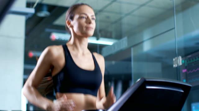 beautiful woman athlete wearing sport bra, walks on a treadmill, training exercise. in the background modern gym/ fitness club. - odzież sportowa filmów i materiałów b-roll