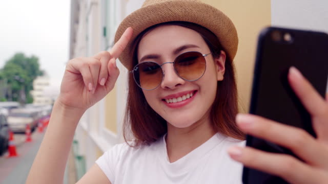 Beautiful woman Blogger or YouTube's Live  is talking and gesturing recording video with smartphone for internet blog , girl is wearing casual clothing live streaming viral online