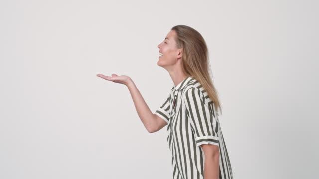 vacker kvinna blåser på öppen hand - blåsa en kyss bildbanksvideor och videomaterial från bakom kulisserna