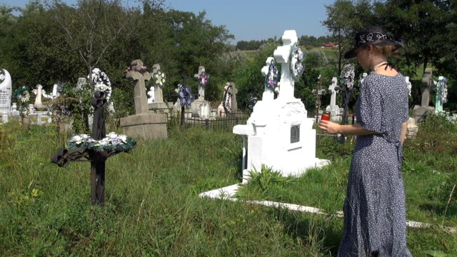 stockvideo's en b-roll-footage met beautiful woman bringing candle in cemetery - funeral crying