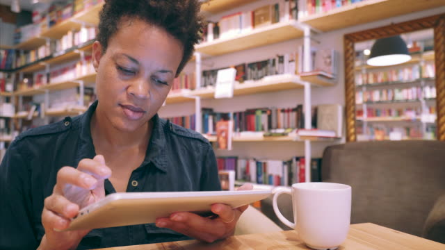 Beautiful woman browsing the internet. Young black ethnicity woman using a digital tablet in a library. She gets to spend some quiet time alone while surfing the internet. short hair stock videos & royalty-free footage