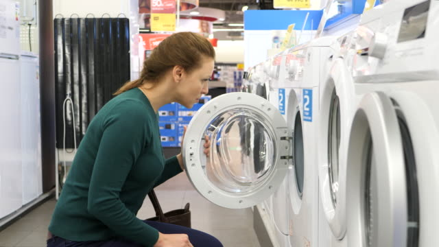 Beautiful woman buying washing machine in supermarket. 4k UHD. woman buying washing machine. 4k UHD. appliance stock videos & royalty-free footage