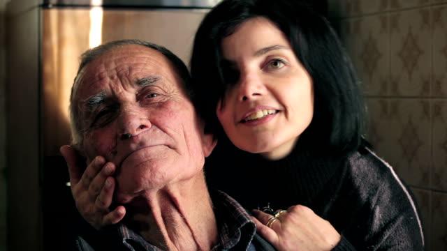 donna bellissima accarezzi e baci suo nonno che guarda alla fotocamera-ballerina - fianco a fianco video stock e b–roll