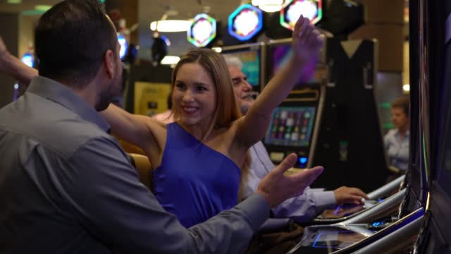 Beautiful woman celebrating she just one at the slot machines sitting next to her partner hugging and smiling