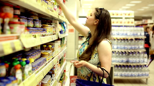 Beautiful woman choosing goods on shelves in supermarket Beautiful woman choosing goods on shelves in supermarket. Housewife checking price in local market on weekend. Girl shopping at market store center on vacation conceptual. market retail space stock videos & royalty-free footage