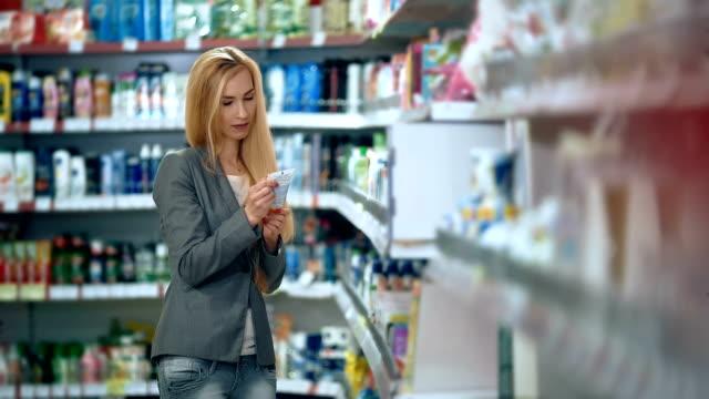 schöne frau körperpflege produktauswahl im supermarkt - kosmetik stock-videos und b-roll-filmmaterial