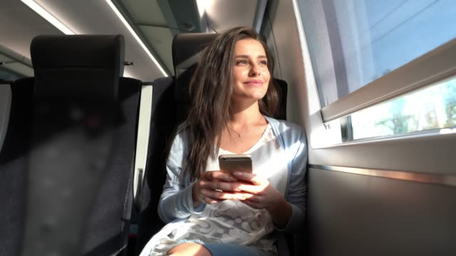 beautiful woman commuting on train texting on her smartphone while looking at view from window seat - montare video stock e b–roll