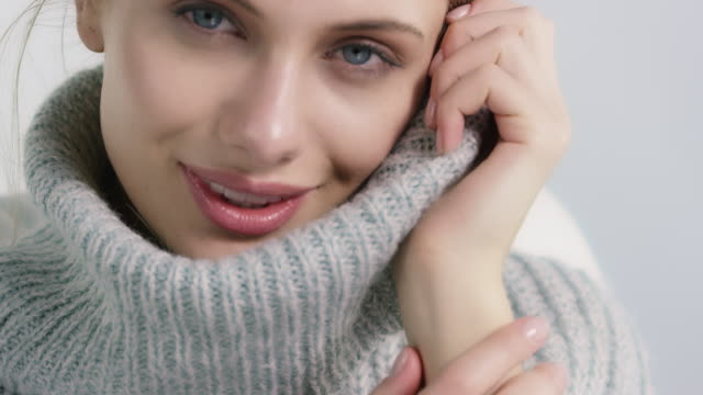 Beautiful woman covering face in soft sweater