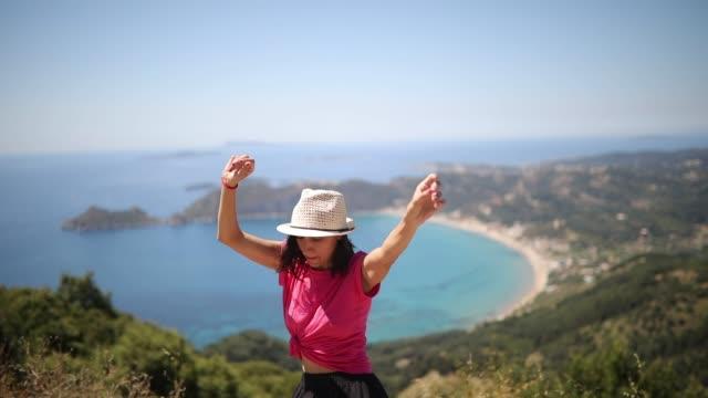 stockvideo's en b-roll-footage met mooie vrouw dansen op het eiland corfu - mid volwassen vrouw
