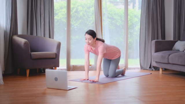 Beautiful woman do yoga posture or move by stretching leg and arms and she look example from laptop in home living room. Concept of workout at home for good health and prevent covid virus infection