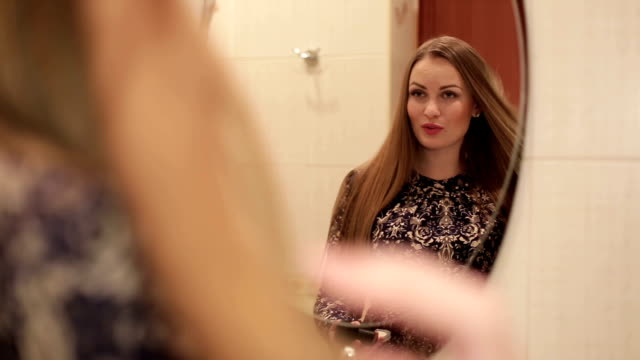 Beautiful woman doing make-up looking at the mirror in the interior of the bathroom in front of large window video