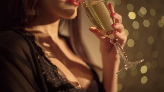 beautiful woman drinking champagne against christmas holiday garland lights - cleavage stock videos and b-roll footage
