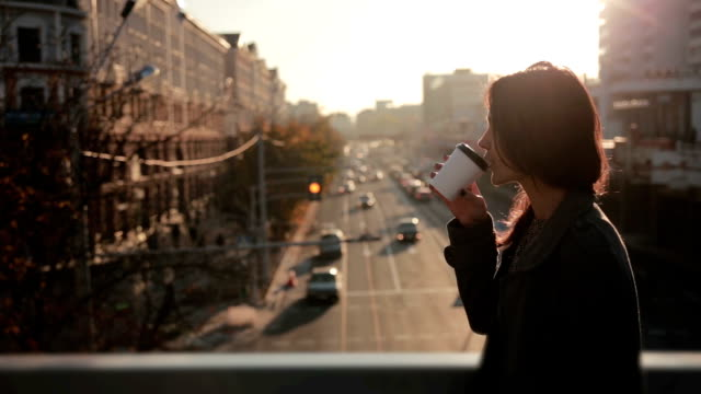 Beautiful woman drinking coffee on a city bridge video