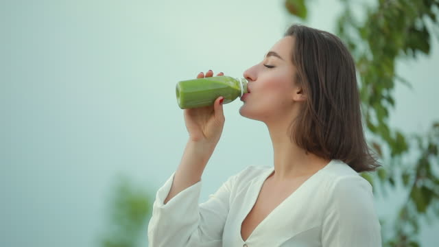 Beautiful woman drinking green smoothie outdoor