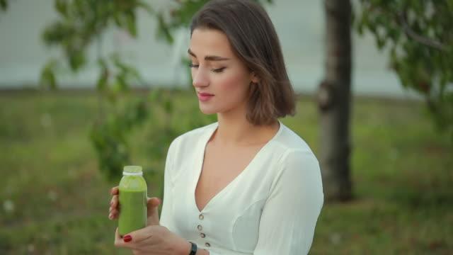 美しい女性を飲む緑のスムージー屋外 - ローフード点の映像素材/bロール