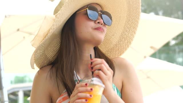 Beautiful woman drinking orange juice on the beach.