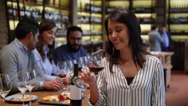 Beautiful woman drinking wine at a cellar while facing camera smiling Beautiful woman drinking wine at a cellar while facing camera smiling - Incidental people at background winetasting stock videos & royalty-free footage