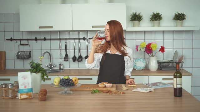 beautiful woman drinking wine in domestic kitchen. redhead girl. - spettinato video stock e b–roll