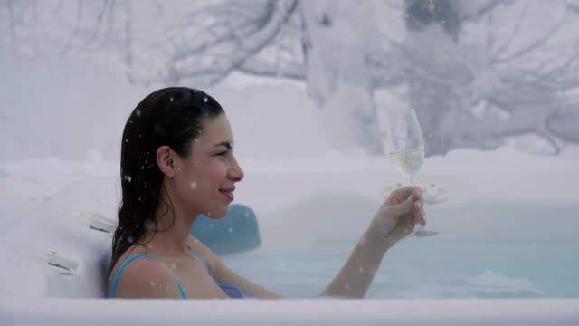 a beautiful woman drinks champagne in a hot tub surrounded by nature as the snow falls from the sky. - купальный костюм стоковые видео и кадры b-roll