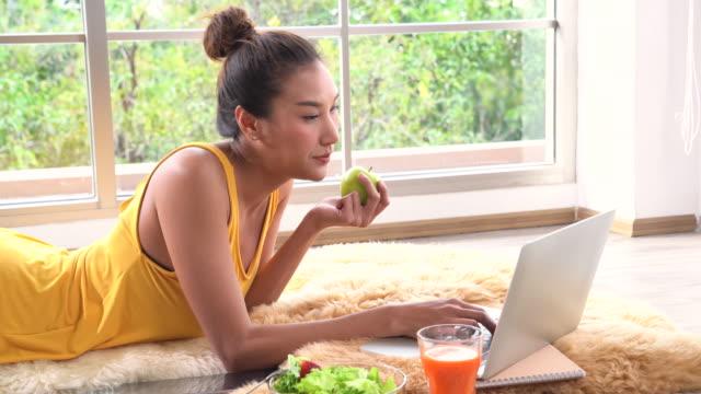 Una hermosa mujer de comer manzana y el uso del ordenador portátil - vídeo