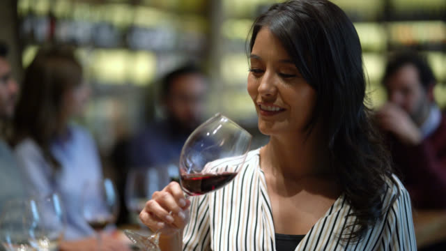 Beautiful woman enjoying a glass of red wine and then facing camera smiling Beautiful woman enjoying a glass of red wine and then facing camera smiling - Focus on foreground winetasting stock videos & royalty-free footage