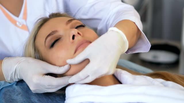 Schöne Frau Gesichts-Massage im Schönheitssalon zu genießen – Video