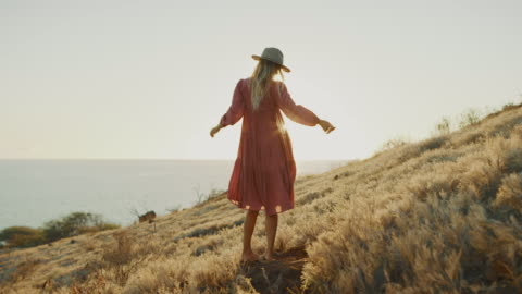 Beautiful woman enjoying sunset in a summer dress Young attractive woman in a flowy pink dress dancing in a golden field at sunset, beautiful artsy bohemian influencer woman posing for a fashion photo shoot boho stock videos & royalty-free footage