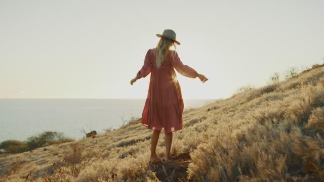 여름 드레스에 일몰을 즐기는 아름다운 여자 - influencer 스톡 비디오 및 b-롤 화면