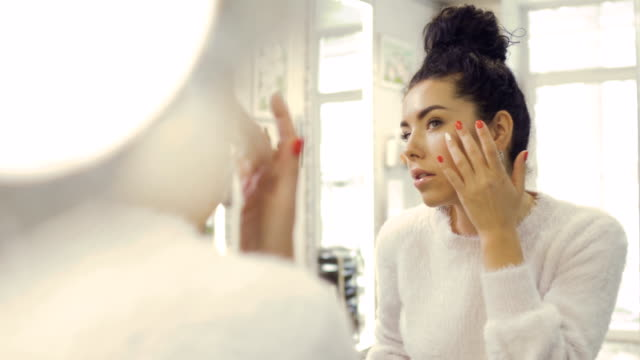 Beautiful woman enjoys her skin looking in the mirror video