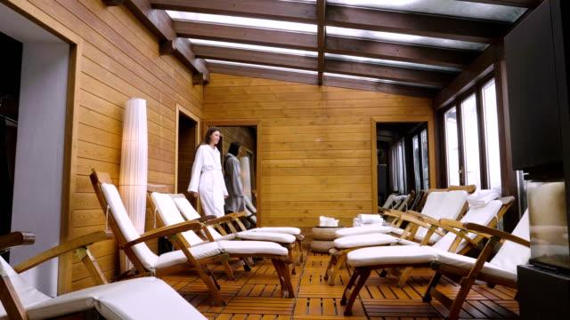 vídeos y material grabado en eventos de stock de una hermosa mujer entra en una sala de relajación de un spa de madera (gimnasio) con un albornoz blanco y se sienta en una de las tumbonas para relajarse. - balneario spa