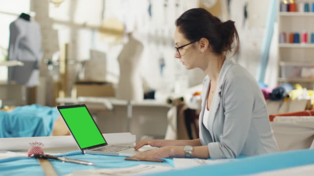 Beautiful Woman Fashion Designer Sitting at Her Desk Working on Laptop with Green Screen. Her Studio is Sunny, Colourful Fabrics and Mannequins are there. video