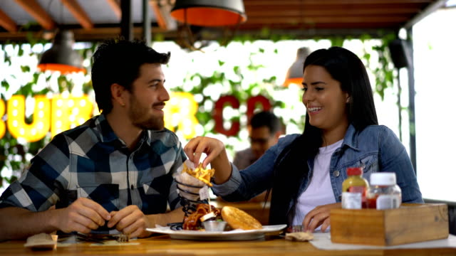 Beautiful woman feeding her boyfriend french fries at a restaurant Couple sharing a hamburger and beautiful woman feeding her boyfriend french fries at a restaurant both looking very happy and talking french fries stock videos & royalty-free footage