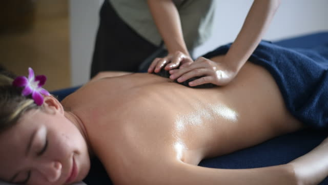 Beautiful woman getting a hot stone massage in spa salon. video
