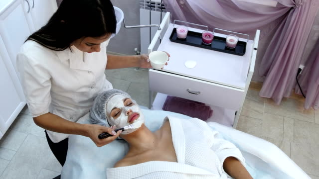beautiful woman getting facial mask at beauty salon - spa facial stock videos & royalty-free footage