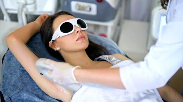 Beautiful woman getting permanent laser hair removal at beauty salon. video