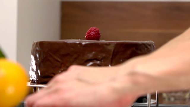 beautiful woman hands placing raspberries onto freshly cooked chocolate cake. fullhd close up video - lega sportiva amatoriale video stock e b–roll