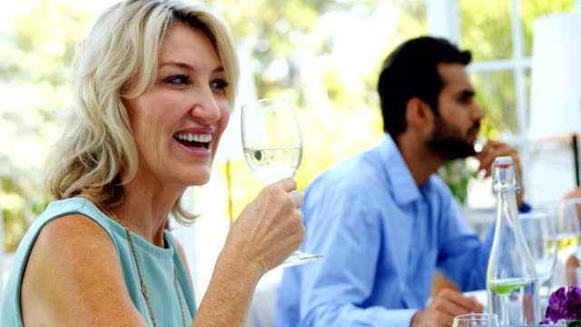 Beautiful woman having glass of wine in restaurant video