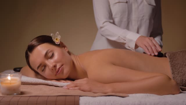 beautiful woman having hot stone massage at spa - terapia lastone filmów i materiałów b-roll