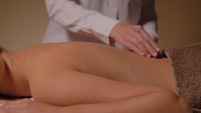 bella donna con massaggio con pietre calde al centro benessere - china drug video stock e b–roll