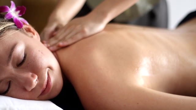 Beautiful woman having relaxing in spa massage salon. video