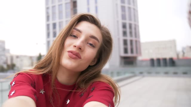 beautiful woman having video chat using smartphone outdoors sharing travel adventure in the city. girl filming selfie video photo for social media - woman chat video mobile phone video stock e b–roll