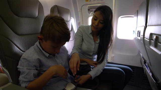 88a67189 Beautiful woman helping a little boy with his seat belt waiting for the  plane to take