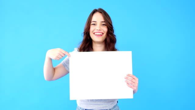 vacker kvinna som håller tomma plakat på blå bakgrund - hålla bildbanksvideor och videomaterial från bakom kulisserna