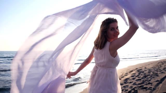 美しいを持っている女性軽いファブリックビーチの、夕日をお楽しみください。 - 布点の映像素材/bロール