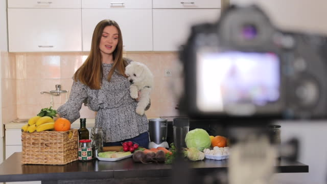 Beautiful woman holding Maltese dog in her arms and recording video blog about healthy food at home